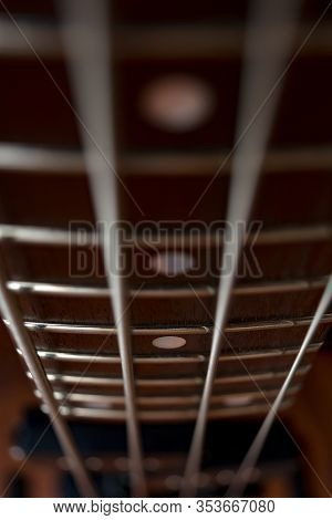 Brown Fretboard Of A Bass Guitar. Four Metal Strings And Metal Frets. Musical Instrument. Low And De