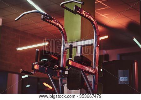 Metallic Parallel Bar Machine Standing In An Empty Modern Fitness Center. Sportive Gym Equipment.