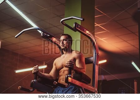 Powerful Athletic Bodybuilder Doing Excersise On A Parallel Bars In A Modern Fitness Center Looking