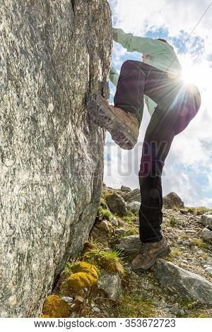 Female Mountaineer Practicing Boulder Climbing Outdoor On Large Boulder.
