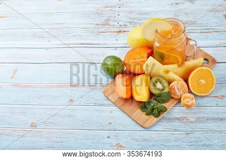 Fruit lemonade with ice, leaves of mint, lemon, pineapple, mango and lime slices standing on blue wooden table. Homemade lemonade with mix fruits. Healthy cool beverage, fruit juice. Top view