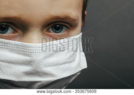 Face of a mask-wearing boy with fear in the eye Close-up on a gray background. Coronavirus and Air pollution pm2.5 concept
