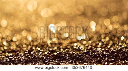 Sparkling Light Boke Blur. Sea Pebbles. Golden Glitter Particles Background.