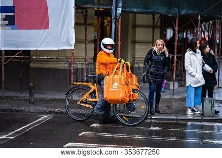 Young Man On An Electric Bike With Takeaway.com Logo Delivering Food During A Rainy Day In Bucharest