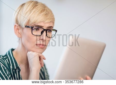 Discontented Mature Businesswoman In Glasses Using Digital Tablet Reading Business News Sitting Indo
