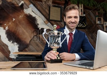 happy business man in suit smiling and holding trophy, sitting in a coffeeshop