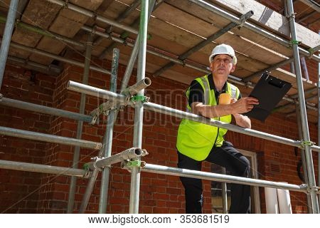 Man, male builder, foreman, construction worker, surveyor, engineer or architect on site holding a clipboard and drinking a mug of coffee or tea