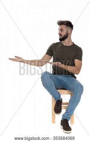 Bothered casual man presenting and explaining while sitting on a chair on white studio background