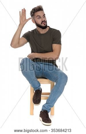 Bothered casual man frowning and gesturing crazy, looking away while sitting on a chair on white studio background