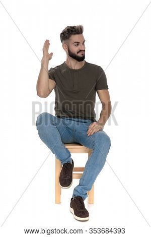 Bothered casual man waving to be left alone while sitting on a chair on white studio background