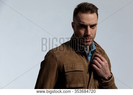 Bothered fashion frowning and adjusting his jacket, standing on gray wallpaper background