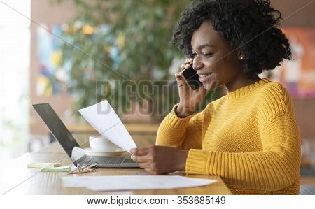 Young Black Smiling Woman Editor Talking To Clients On Phone, Working With Laptop At Cafe