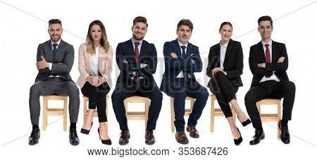 Team of 6 trustworthy businessmen smiling and looking forward while sitting on chairs on white studio background