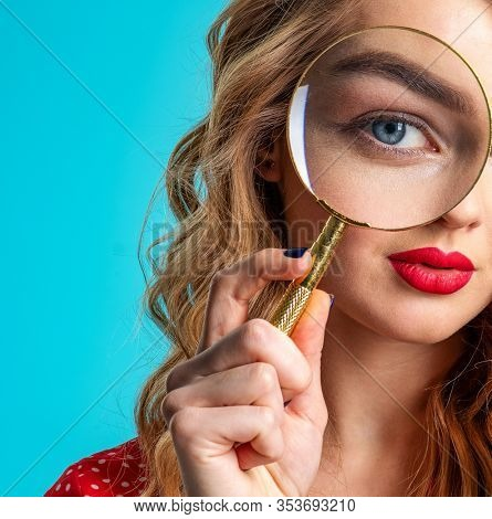 Blonde holds a magnifying glass in front eye. Young woman holds a magnifying glass in front of her eye. Funny girl with a bright smile and loupe. Funny girl. Eyesight care. Funny face of a girl