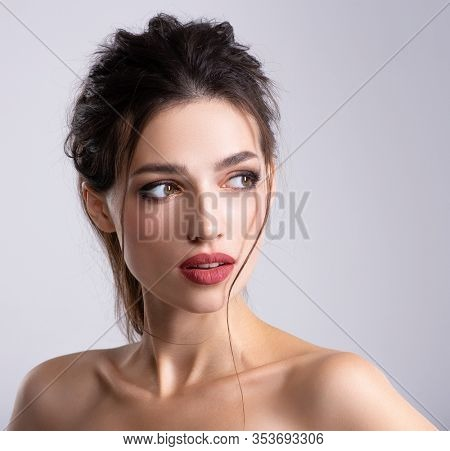 Woman with beauty brown hair. Portrait of brunette woman with beautiful long hairstyle. Fashion model posing at studio. Beautiful young woman with long brown hair. Pretty model poses at studio.