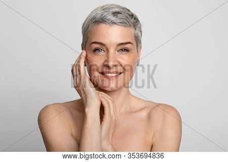 Aged Beauty. Portrait Of Attractive Nude Mature Lady With Smooth Skin Smiling To Camera, Posing Over