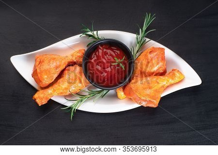 Raw Chicken Marinated Legs On A White Plate With Different Spices And Peppercorns On A Black Backgro