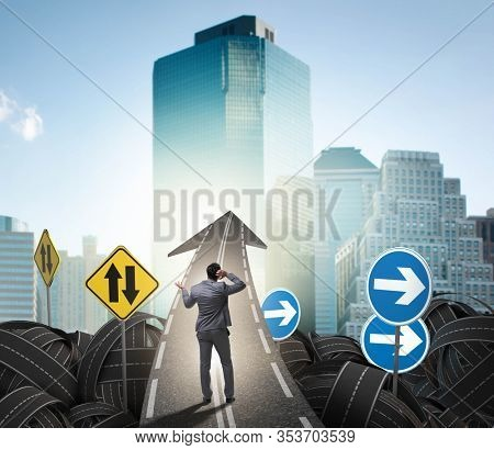 Businessman in uncertainty concept on road intersection crossroa