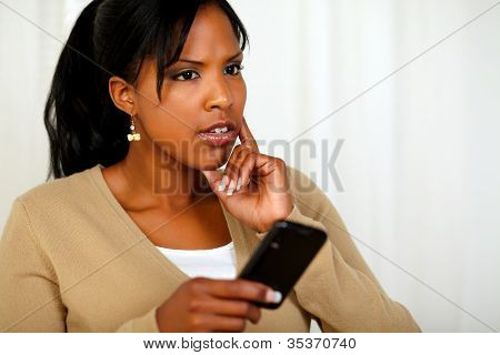Pensive Young Woman Using Her Cellphone