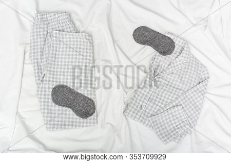 Sleepwear For Slumber. Grey Pajamas For Men. Sleeping Mask On White Sheet In Bedroom. Top View. Flat