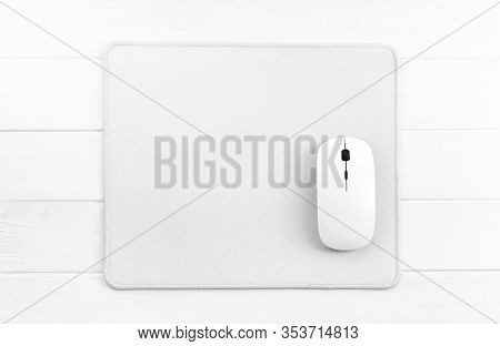 Computer mouse on white mouse pad, top view