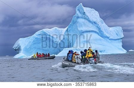 Charlotte Bay, Antarctica - December 26, 2019 Tourists Rubber Boats Large Blue Iceberg Charlotte Bay