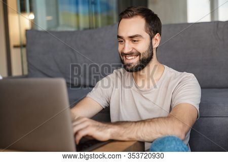 Image of a happy optimistic young man indoors at home using laptop computer.