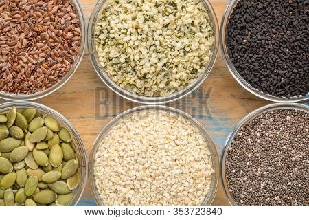 healthy seed collection (chia, hemp hearts, brown flax, pumpkin, black cumin, white sesame) - top view of small glass bowls against grunge wood