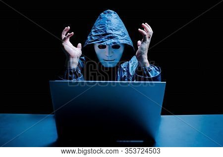 Anonymous Computer Hacker In White Mask And Hoodie. Stressful Male Hacker Screaming On A Damaged Lap