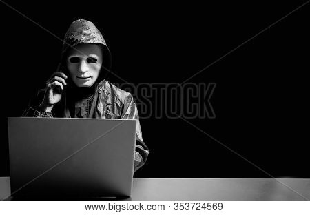 Anonymous Computer Hacker In White Mask And Hoodie. Obscured Dark Face Using Laptop Computer For Cyb