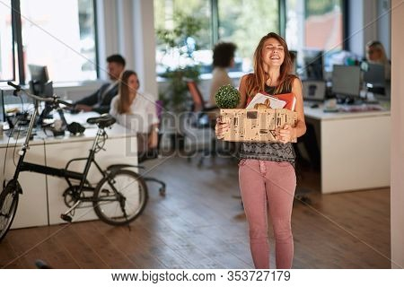 New job at  successful modern business company.Smiling Girl moving box with stuff at new office.
