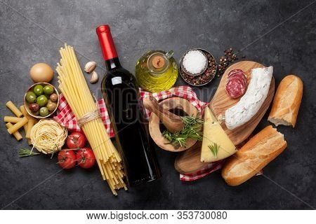 Italian cuisine food ingredients. Pasta, cheese, salami, olives and wine. Top view flat lay on stone table