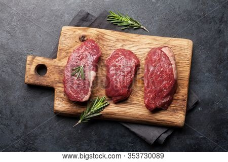 Fillet mignon fresh raw beef steaks with spices on cutting board. Top view flat lay