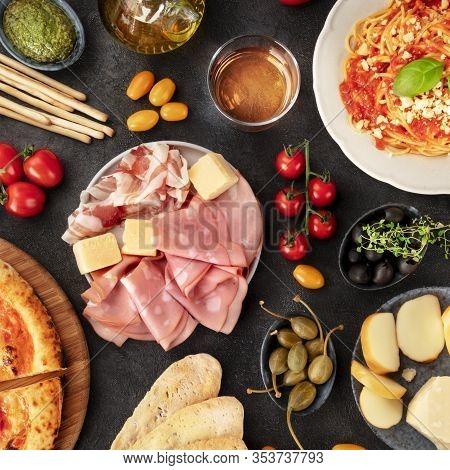 Italian Food, Top Shot On A Black Background. Antipasti, Spaghetti, Cheese, Ham, Capers, Wine, Olive