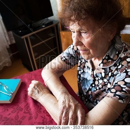 Old woman. Sad elderly female at home