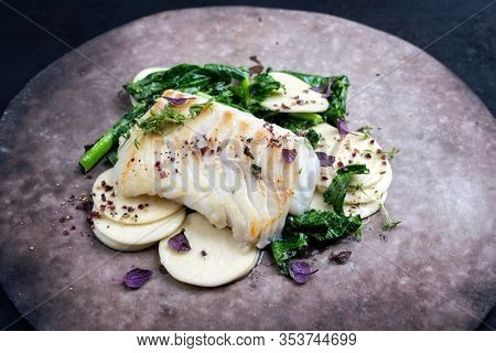 Gourmet fried European skrei cod fish filet with rapini broccoli rabe and creoxetti pasta as closeup on a modern design plate