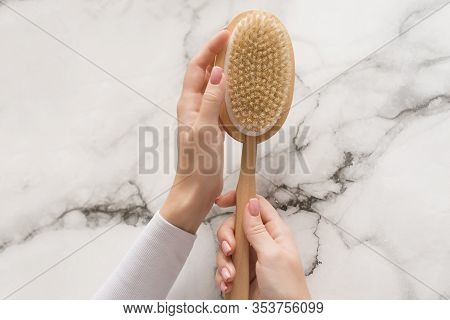 Brush For Dry Massage In The Hands Of A Girl On A Marble Background. Brush For Scrubbing The Body, B