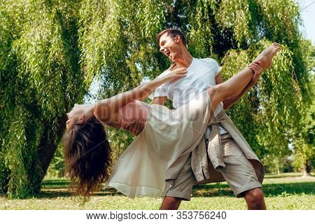 Horizontal Image Of Romantic Couple In Love Dating Outdoors At The Park On A Sunny Day. Happy Couple