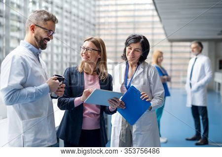 Group Of Doctors Talking To Pharmaceutical Sales Representative.