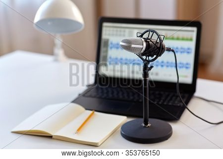 post production and technology concept - microphone, laptop computer with sound editor program, headphones and notebook on table at home office