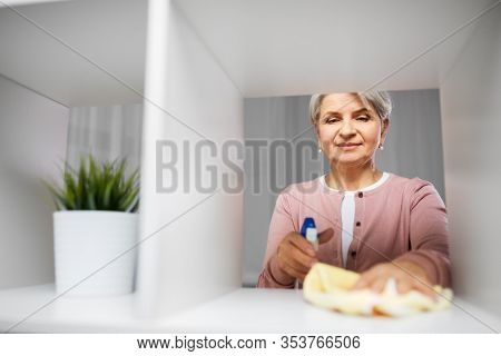 people, housework and housekeeping concept - happy senior woman with dusting cloth and detergent cleaning rack at home