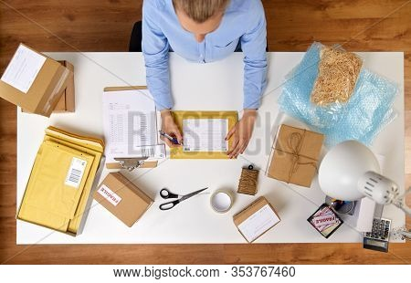 delivery, mail service, people and shipment concept - close up of woman filling postal form on envelope parcel box at office