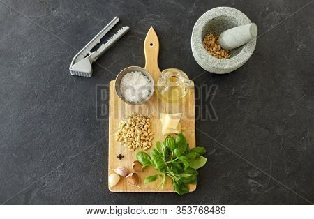 food cooking and culinary concept - mortar with pestle, parmesan cheese, pine nuts, vinegar and garlic for basil pesto sauce making on wooden cutting board