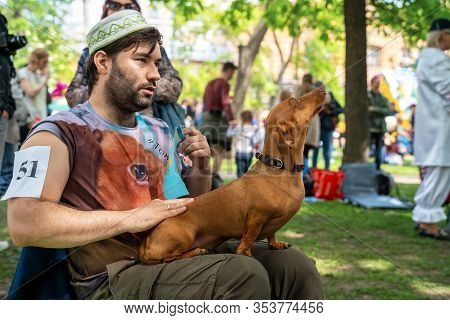 Russia, St. Petersburg, May 25, 2019: Event With Dogs And Owners Called Dachshund Parade. Sitting Ma