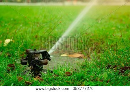 Automatic Lawn Sprinkler Watering Green Grass. Garden, Yard Irrigation System Watering Lawn. Water S