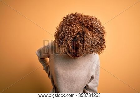 Young beautiful african american woman wearing turtleneck sweater over yellow background Suffering of backache, touching back with hand, muscular pain