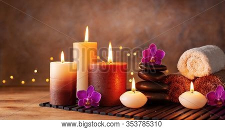 Spa, Beauty Treatment And Wellness Background With Massage Stone, Orchid Flowers, Towels And Burning