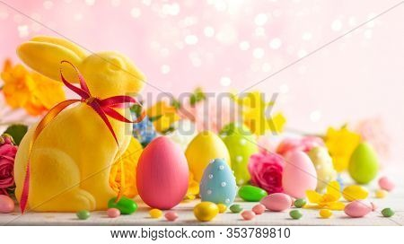 Easter decoration with Easter eggs, colorful rabbits and spring flowers on white wooden table. Easter concept with copy space.