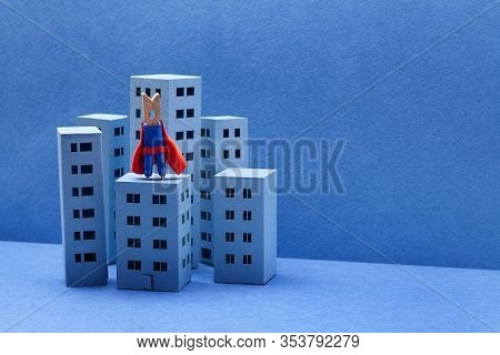 Super Clothespin Peg Hero In Red Blue Costume. Brave City Defender On The Top Of High-rise Building.