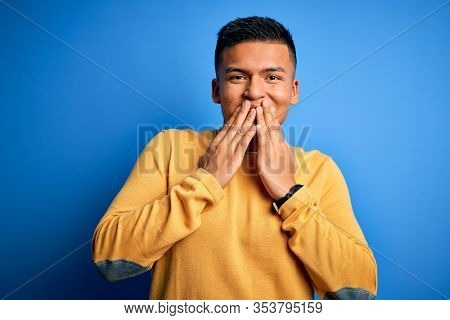 Young handsome latin man wearing yellow casual sweater over isolated blue background laughing and embarrassed giggle covering mouth with hands, gossip and scandal concept